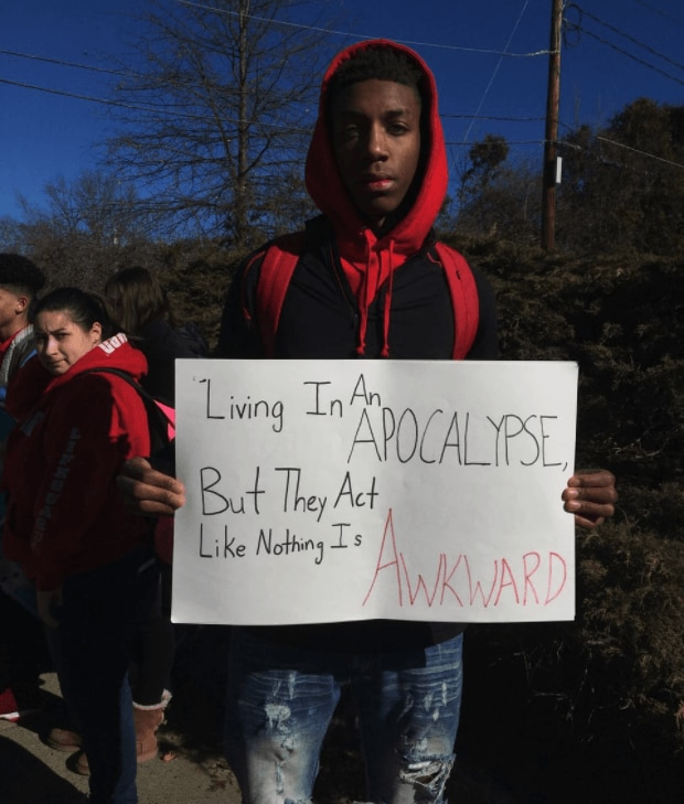 Calvin Bridges, a senior at South Hadley High School, held a sign during the walkout. thegrio.com