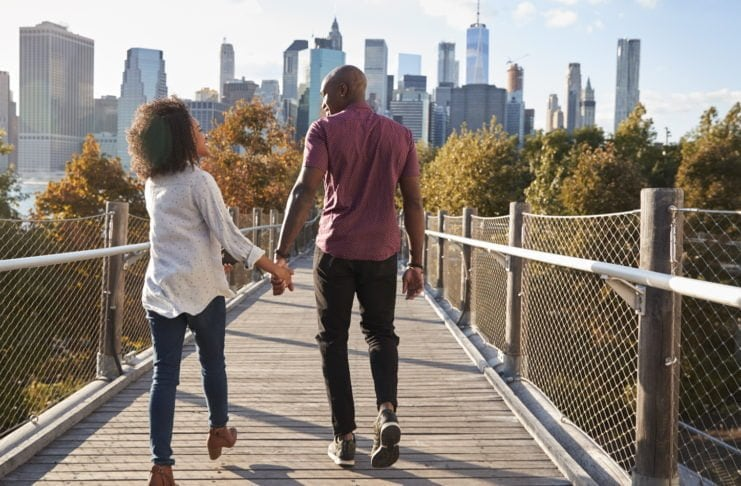 Couple Visiting New York With Manhattan Skyline In Background thegrio.com