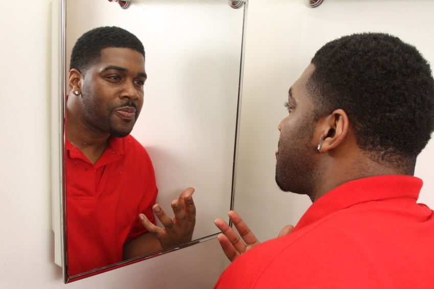 man looking at himself in the mirror thegrio.com