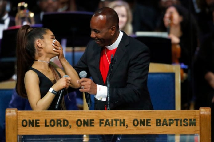 Ariana Grande, left, laughs with Bishop Charles H. Ellis during the funeral service for Aretha Franklin at Greater Grace Temple, Friday, Aug. 31, 2018, in Detroit. Franklin died Aug. 16, 2018 of pancreatic cancer at the age of 76. (AP Photo/Paul Sancya)