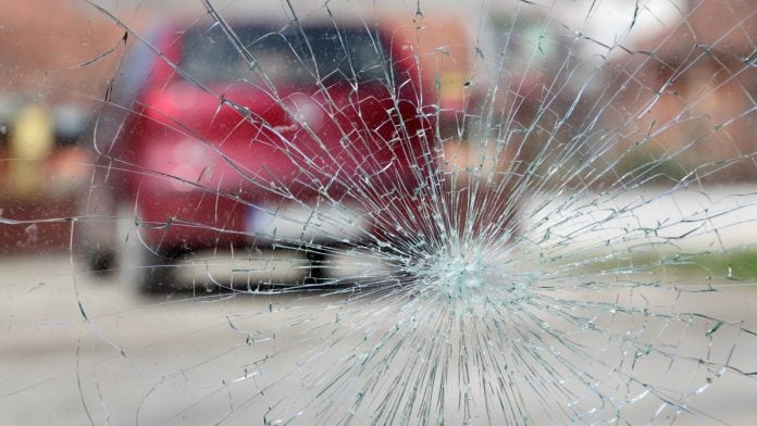 Broken windshield with red car in background