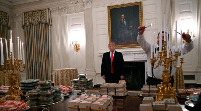 n this Jan. 14, 2019 photo, President Donald Trump talks to the media about the table full of fast food in the State Dining Room of the White House in Washington, for the reception for the Clemson Tigers. The partial government shutdown is hitting home for President Trump in a very personal way. He lives in government-run housing, after all. Just 21 of the roughly 80 people who help care for the White House _ from butlers to electricians to chefs _ are reporting to work. The rest have been furloughed. (AP Photo/Susan Walsh) thegrio.com