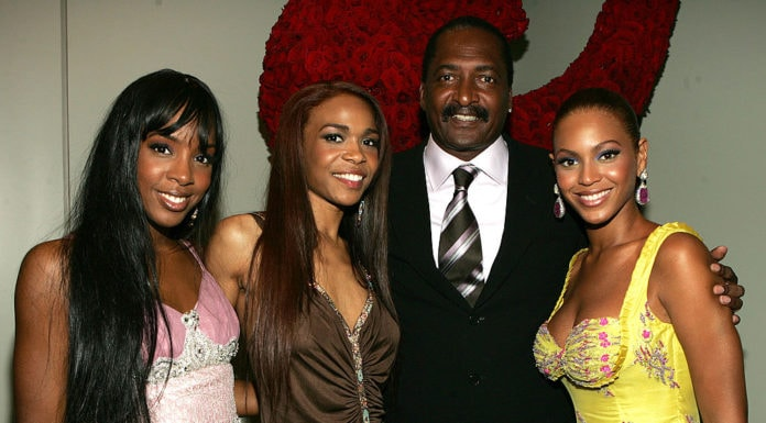 "Singers Kelly Rowland, Michelle Williams and Beyonce Knowles pose with their manager Matthew Knowles at the ""Beyonce: Beyond the Red Carpet auction presented by Beyonce and her mother Tina Knowles along with the House of Dereon to benefit the VH1 Save The Music Foundation June 23, 2005 in New York City. (Photo by Frank Micelotta/Getty Images) thegrio.com"