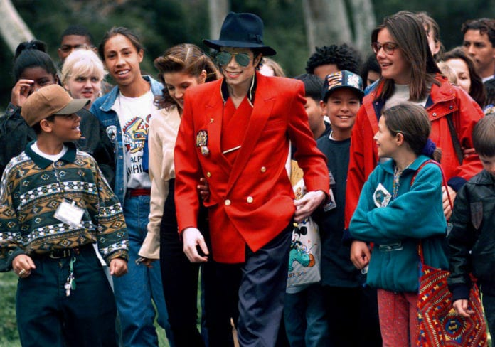 In this April 18, 1995, file photo, pop star Michael Jackson and Lisa Marie Presley, behind him at left, walk with children that were invited guests at his Neverland Ranch home in Santa Ynez, Calif. The co-executor of Jackson's estate says he's confident the late superstar's supporters will be able to protect his legacy and brand in the wake of HBO's