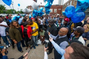 Guests gather and listen to community leaders speak during a vigil for Eric Logan Monday, June 17, 2019 on Washington Street in South Bend, Ind. Logan, 54, was killed in South Bend early Sunday after someone called police to report a suspicious person going through cars, according to the St. Joseph County prosecutor's office. (Michael Caterina/South Bend Tribune via AP)