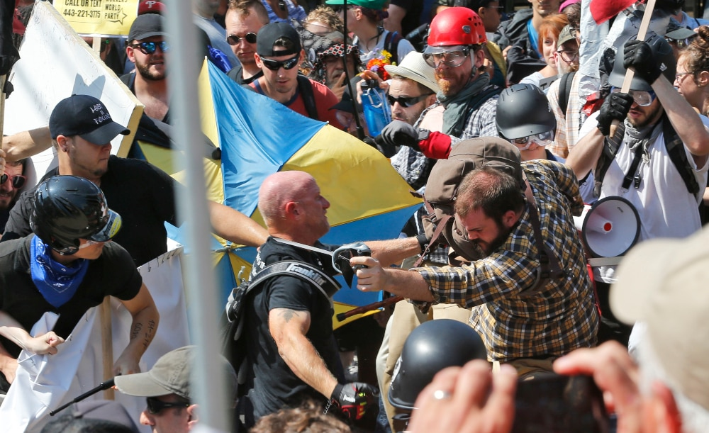 In this Aug. 12, 2017 file photo, white nationalist demonstrators clash with counter demonstrators at the entrance to Lee Park in Charlottesville, Va. Three alleged members of a white supremacist group accused of inciting violence at California political rallies were cleared of federal charges after a judge found their actions amounted to constitutionally protected free speech. The judge in Los Angeles on Monday, June 3, 2019 threw out charges of conspiracy to commit rioting and travel or use of commerce with intent to riot against the men. Prosecutors were disappointed with the ruling and reviewing grounds for appeal. (AP Photo/Steve Helber, File)