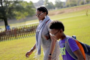 """In this Oct. 11, 2017 file photo, Corrie Davis, left, picks up her son Turner from Big Shanty Elementary School in Kennesaw, Ga. The previous month, the school invited fifth-graders to dress up as characters from the Civil War. Davis says a white student dressed as a plantation owner approached her son and said """"You are my slave."""" She requested that the school to stop the annual Civil War dress-up day. Recently, an investigation by New York Attorney General Letitia James found in May that a mock """"slave auction"""" that singled out black students at the private Chapel School in Westchester County had a profoundly negative effect on all involved students. (AP Photo/David Goldman, File)"""