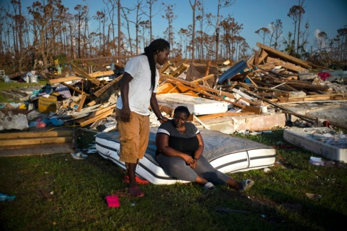 Synobia Reckley pauses on a wet mattress as her husband Dexter Edwards consoles her amid the remains of their home destroyed by Hurricane Dorian in Rocky Creek East End, Grand Bahama, Bahamas, Sunday, Sept. 8, 2019. The couple married two days after Hurricane Mathew hit in 2016 but did not do serious damage. (AP Photo/Ramon Espinosa) thegrio.com
