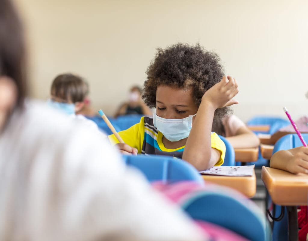 Black chool boy wearing mask and study in classroom