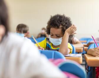 Black chool boy wearing mask and study in classroom