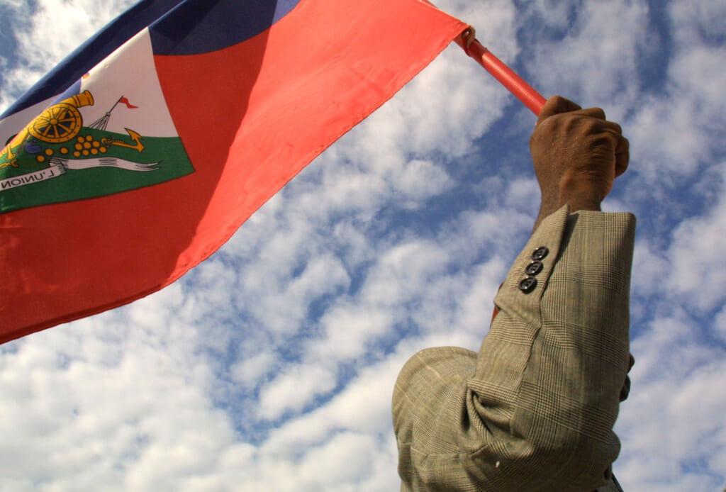 A man holds a Haitian flag
