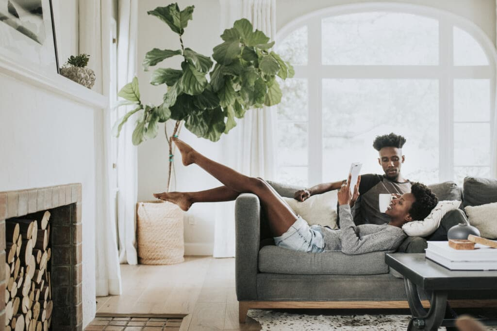 Black couple reading a book on the couch