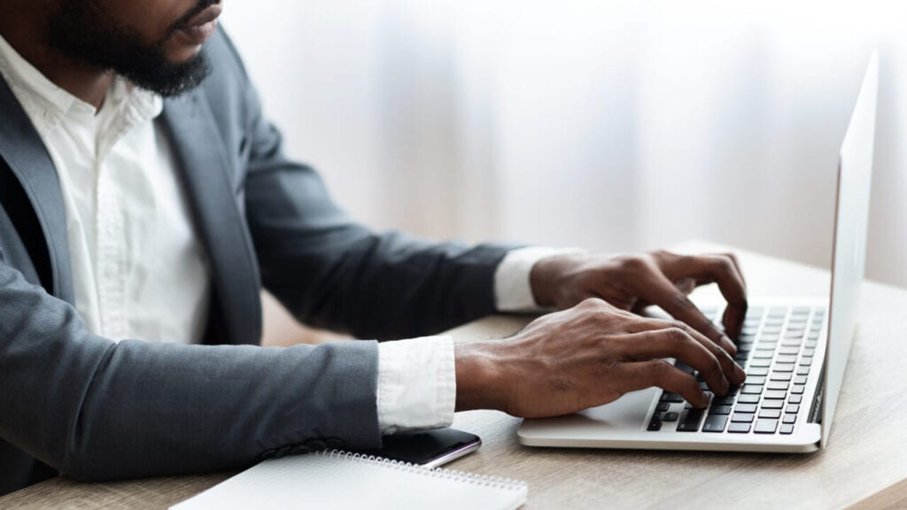 Black man in suit works on computer