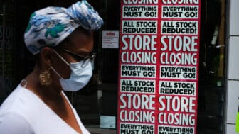 """Black woman in front of """"Store Closing"""" sign on business, theGrio.com"""