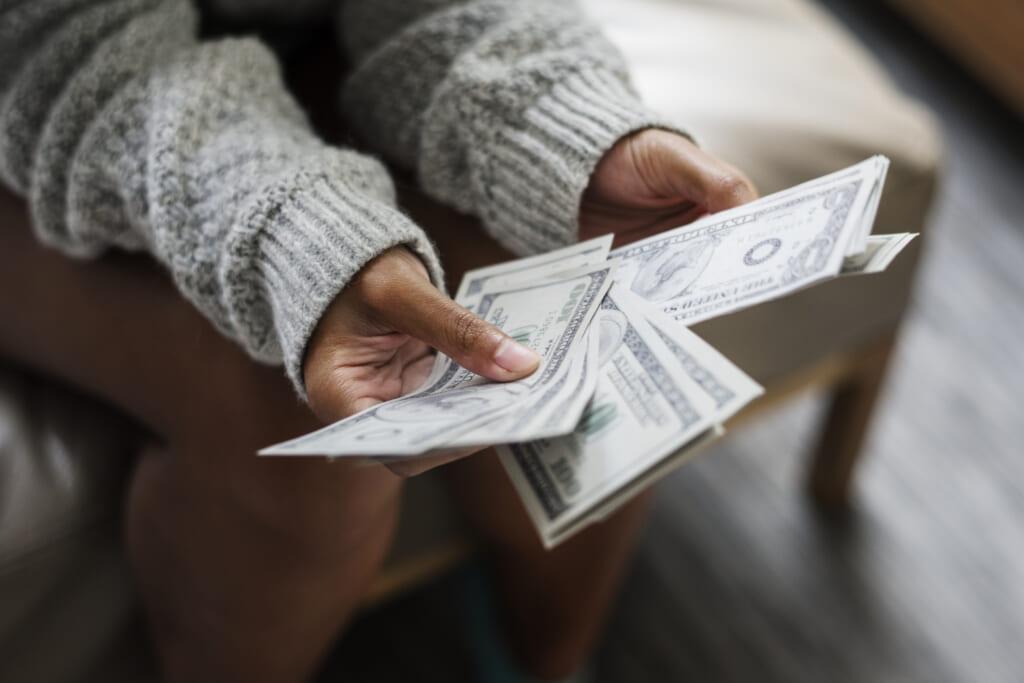 Black woman holds money, theGrio.com
