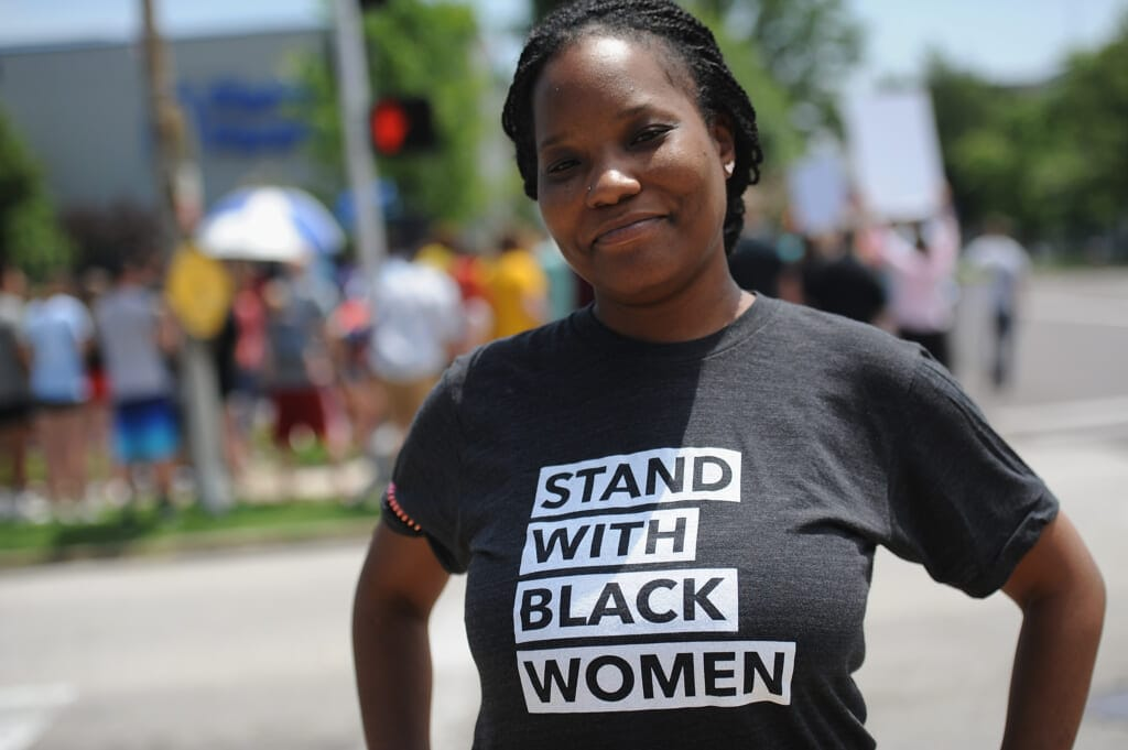 """Black woman in """"Stand with Black women"""" t-shirt, theGrio.com"""