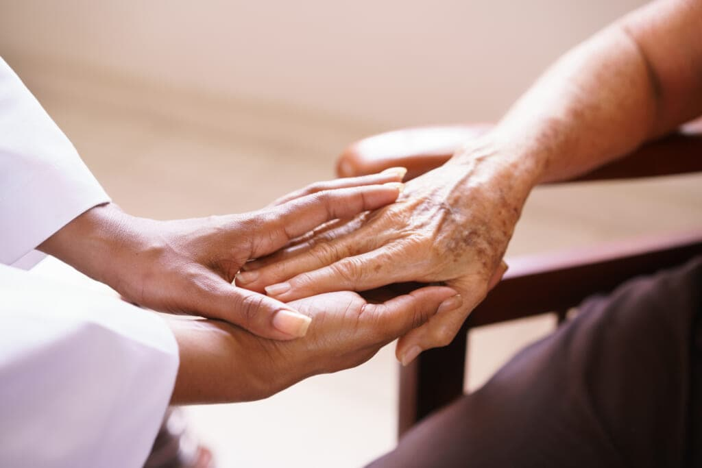 Home care attendant holds elderly person's hand