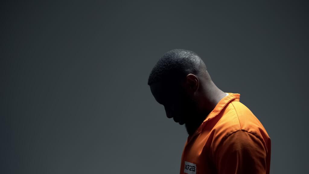 Black man in orange jumpsuit in prison